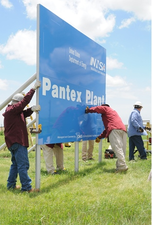 Workers put up a new entry sign at the Pantex
