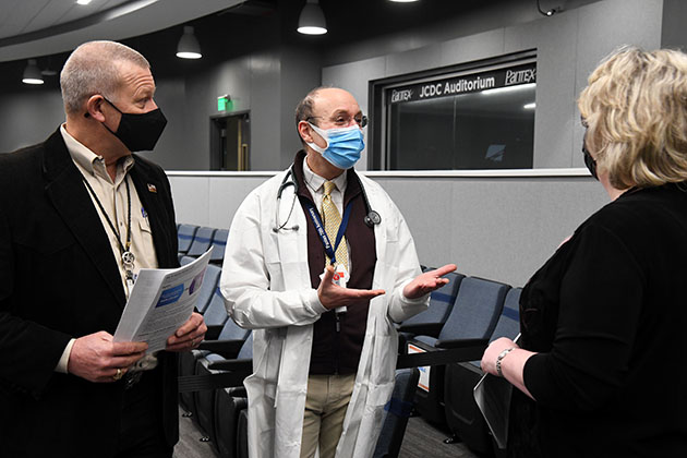 Dr. Paston (center) talks to Geoff Beausoleil, manager of the NNSA Production Office, and Michelle Reichert, CNS president and chief executive officer, at the vaccination clinic.