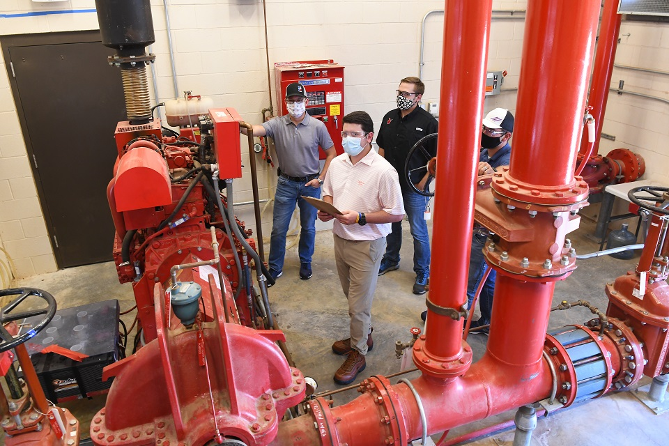 Pantex summer intern Drew Rowlands (center) checks a pump station system with coworkers Jonathan Burkhead (left), Ronnie Anderle (black shirt), and Colton Mooney (right).