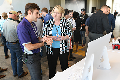 Pantex summer intern Bryan explains his summer project to Chief Operating Officer Michelle Reichert during the Intern Expo
