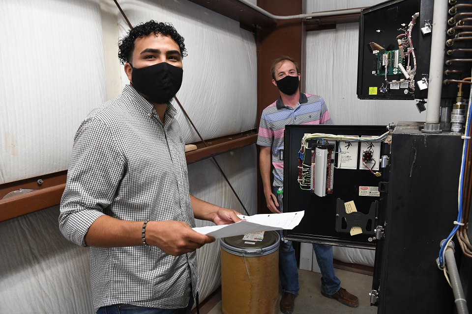 Pantex summer intern Hector Rivero-Figueroa, left, works on a compressor air filter design with coworker Clint Hanes. Social distancing and face coverings were the norm during internship 2020.